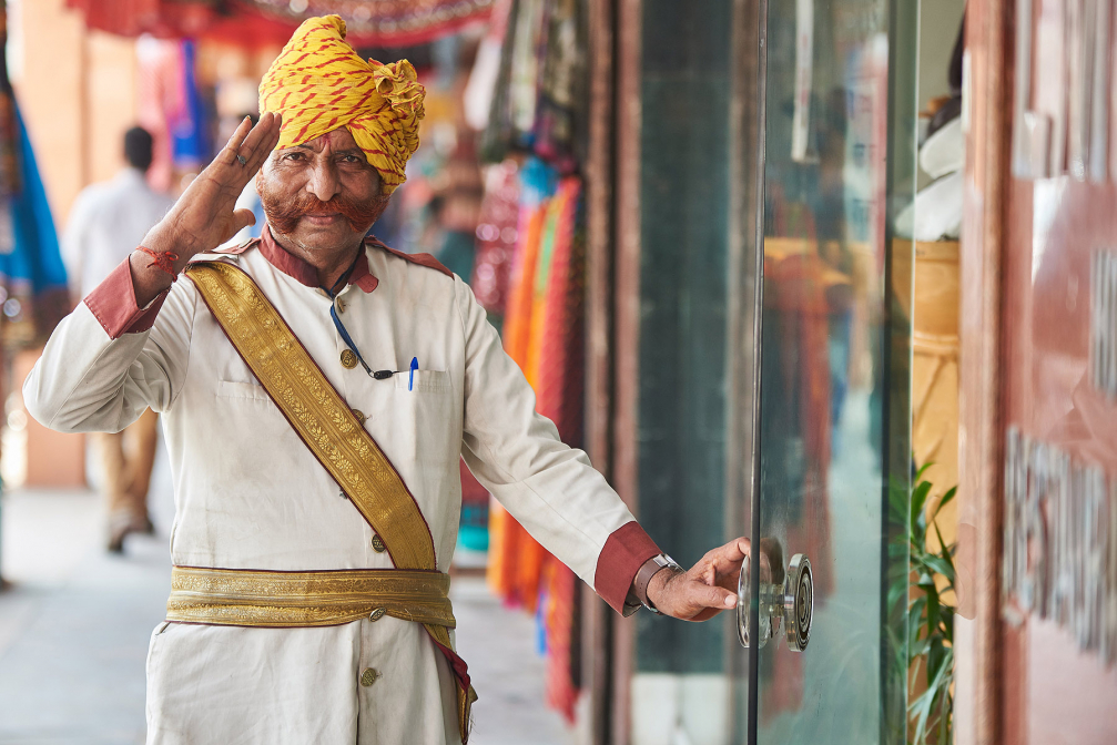 Smart dressed man welcome to Indian shop in Delhi